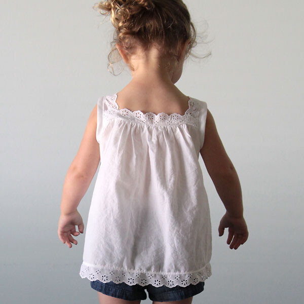 A young girl in a white blouse with lace at the hem, neckline, and straps