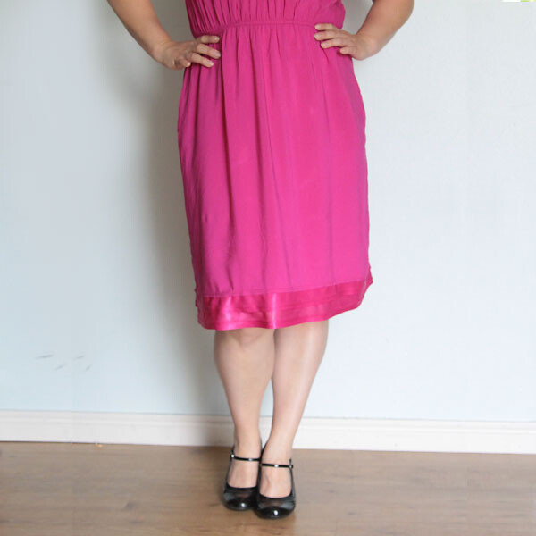 A woman wearing a pink dress that has been made longer using the lining