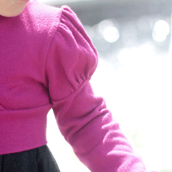 A girl wearing a pink sweater with puffed sleeves