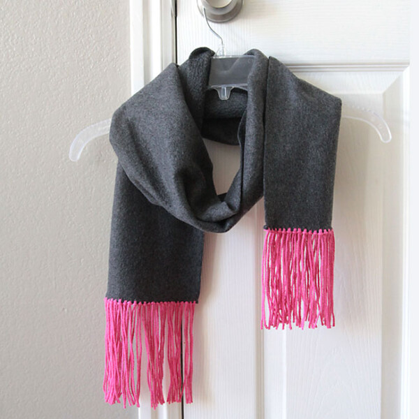 a fleece scarf with yarn fringe hanging on a hanger