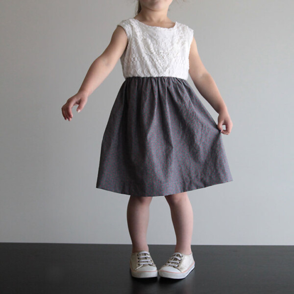 A little girl wearing a dress with gathered skirt