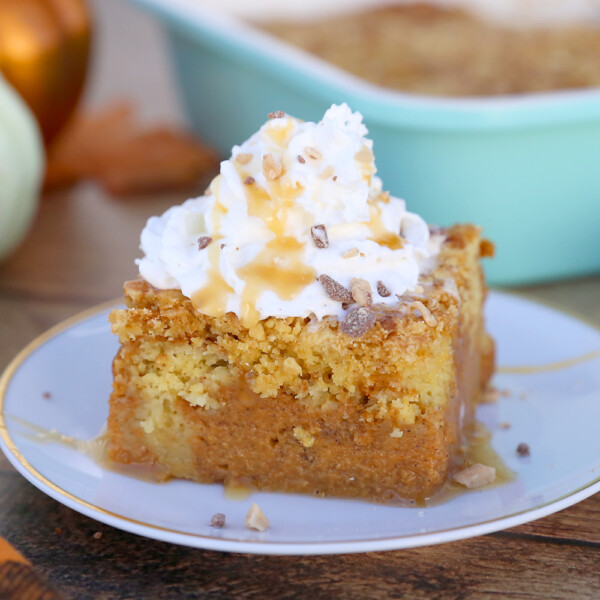 A piece of pumpkin pie cake on a plate, topped with whipped cream and toffee bits