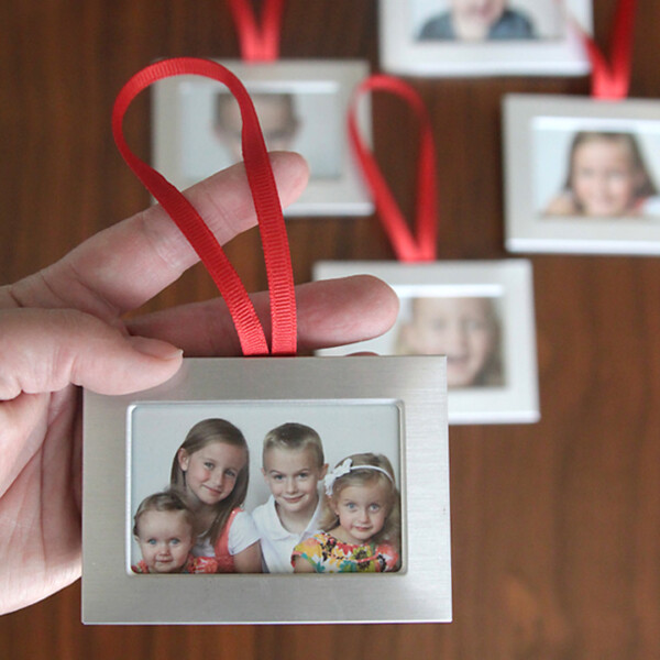 hand holding small silver frame with photo of kids in it and red ribbon loop