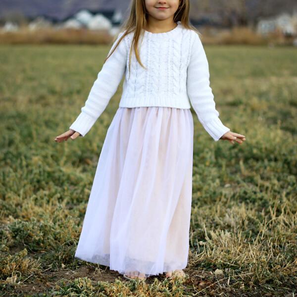 A little girl standing in a field wearing a long skirt