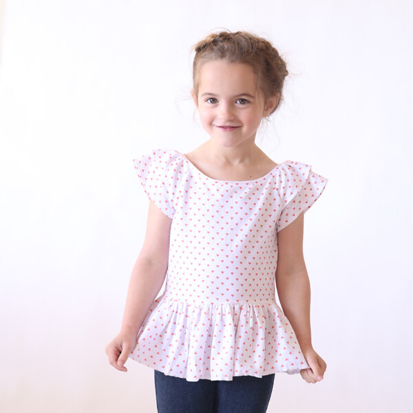 A little girl wearing a flutter sleeve top that was made from a free sewing pattern