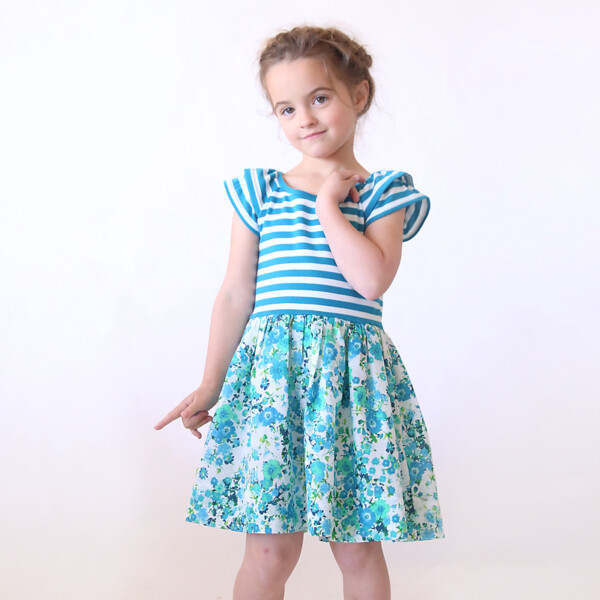 A little girl posing for a picture wearing a dress made from a sewing pattern