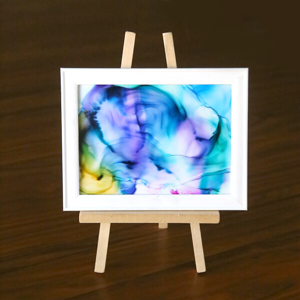 A piece of glass with marbled ink design on it in a frame
