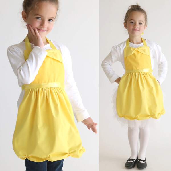A little girl wearing a yellow apron that looks like Belle's dress from beauty and the beast