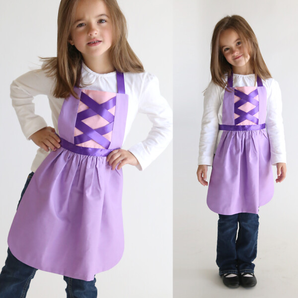 A girl wearing a pink and purple Rapunzel princess dress up apron made from a free pdf sewing pattern