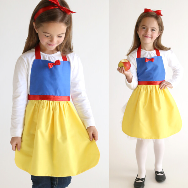 A young girl wearing a Snow White princess dress up apron, holding an apple