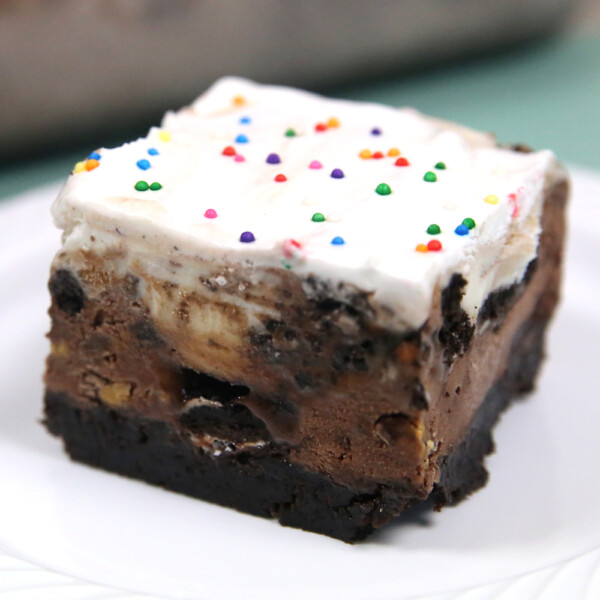 A piece of brownie ice cream cake with sprinkles on top