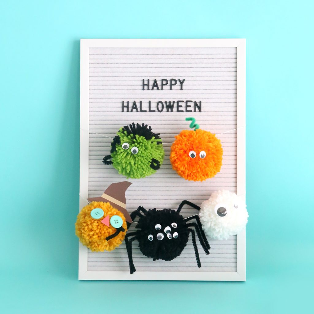 Halloween pom pom characters hanging on a sign that says Happy Halloween