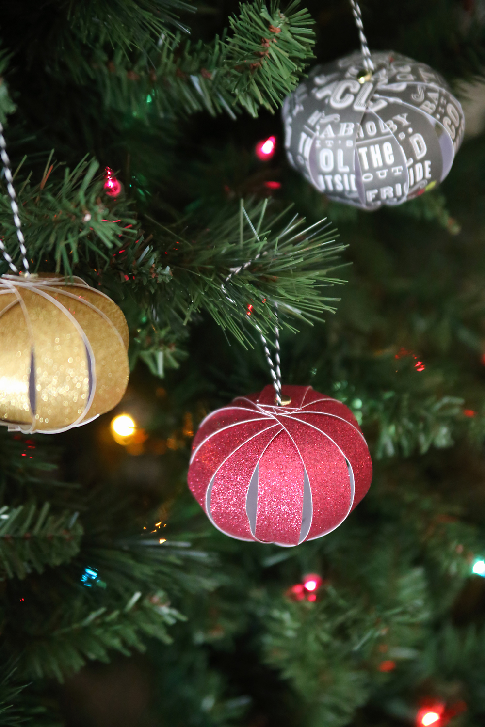 these pretty ornaments are made out of strips of scrapbook paper