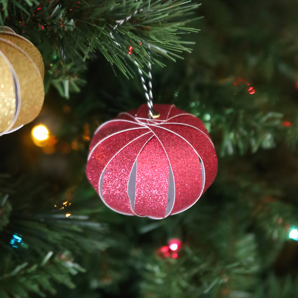 these pretty ornaments are made out of strips of scrapbook paper i have so much