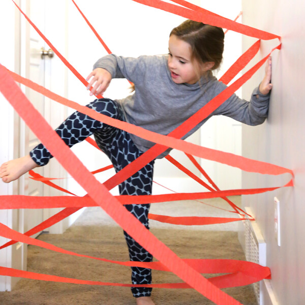 Girl crawling through maze made from crepe paper in a hallway