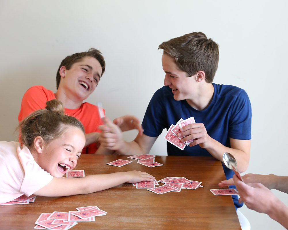 kids laughing playing spoons card game