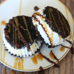 Two Oreo ice cream sandwiches on a plate with caramel and hot fudge