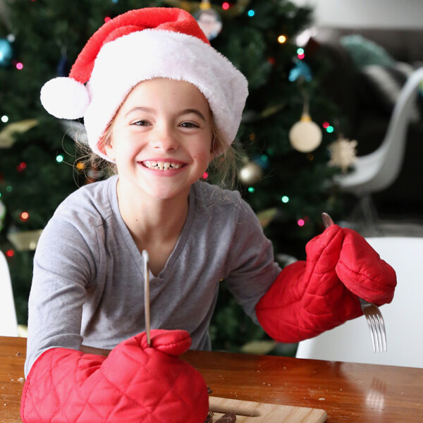 Girl in Santa hat and oven mitts cutting chocolate bar with a fork and knife