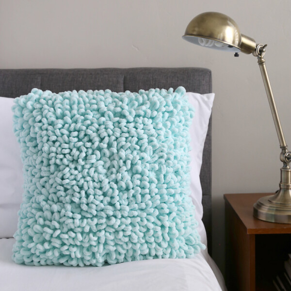 A throw pillow with a soft loopy texture on a bed
