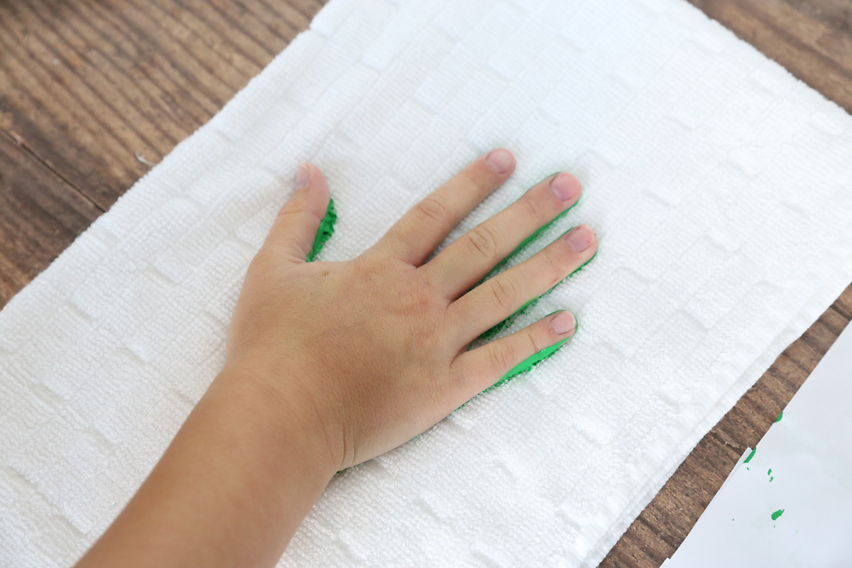 Place the painted hand down on the towel, creating and handprint