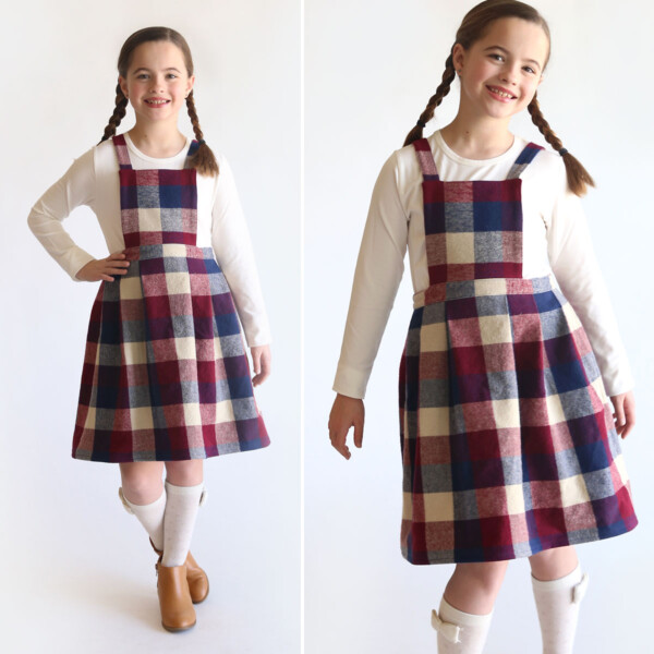 A girl wearing a plaid pleated pinafore dress