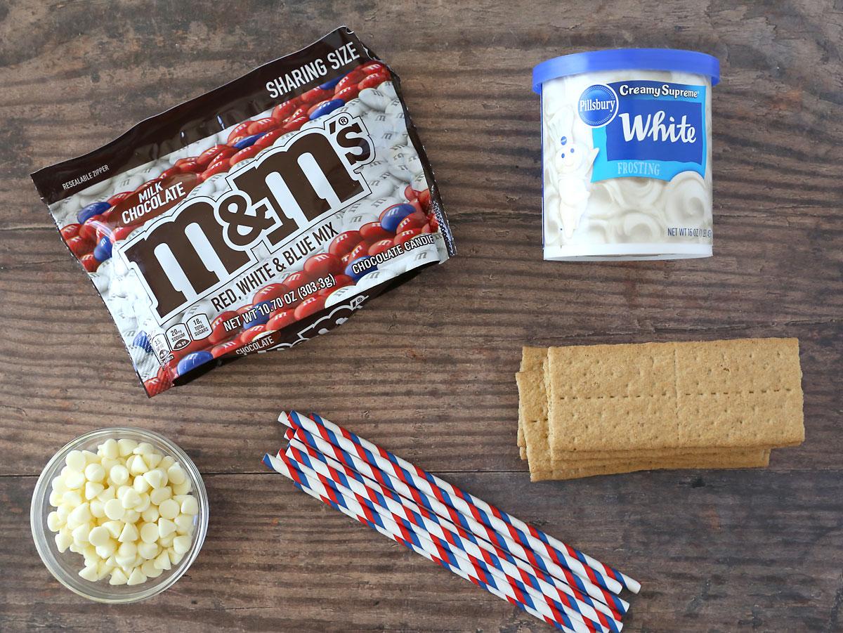 Graham cracker flag ingredients: M & Ms, Graham crackers, frosting, white chocolate chips, straws