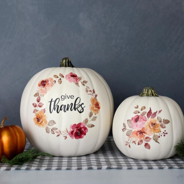 """White craft pumpkins with floral designs and the words """"give thanks"""" on them"""