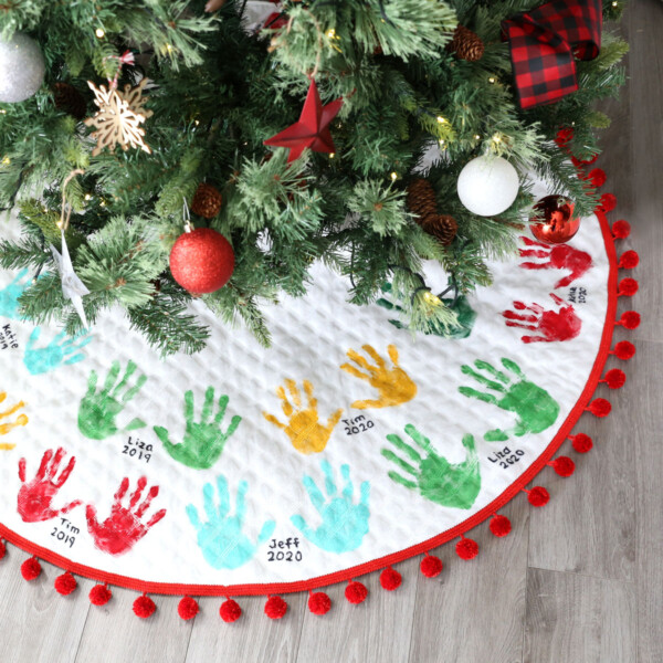 Christmas tree with tree skirt that has kids' handprints on it