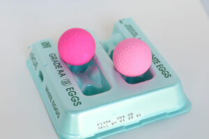 Two golf balls painted pink drying on top of an egg carton