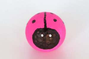 Golf ball painted pink with face drawn in black sharpie and black line and dots on the top
