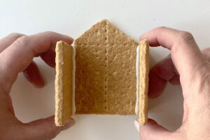 Hands holding graham cracker pieces together to form a house