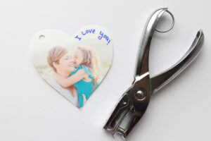 Picture of a girl and her mom printed on shrink film, with keychain attachment and hole punch