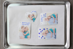 Photos with notes written on them on a parchment paper lined cookie sheet