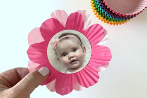 Two cupcake liners cut into flower shape layered on top of each other, with circular baby photo in the center