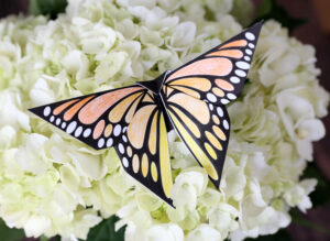 Folded origami monarch butterfly made of colored paper resting on white flowers