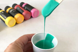 Popsicle stick scooping up paint from a small cup; paint easily runs back into the cup