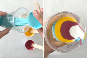 Different colors of paint being carefully poured and layered into a clear cup